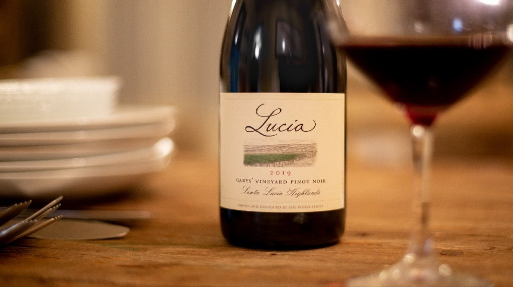 close up of bottle of lucia garys vineyard pinot noir on wooden table